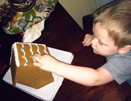 Toddler builds gingerbread house